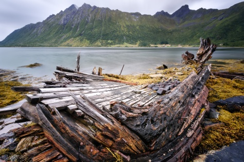An old sunken ship lay on the seashore in Lofoten islands, Norway